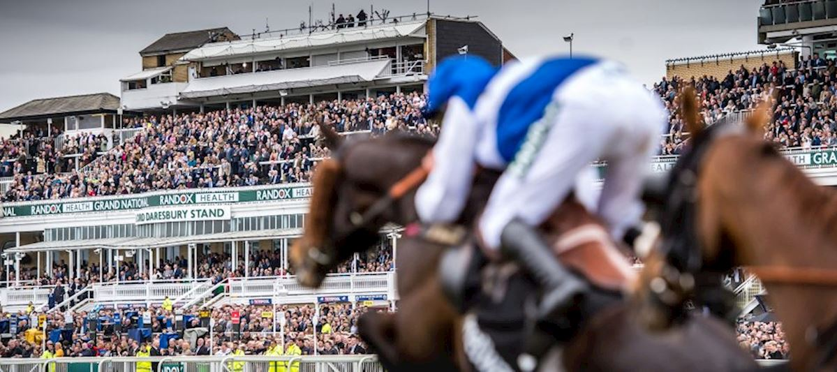 a close up of a horse running past the aintree racecourse grandstands on a busy day
