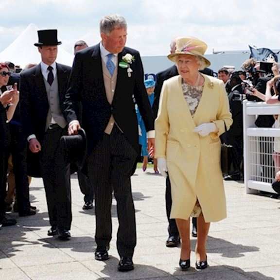 Epsom Downs Chairman Anthony Cane walking alongside H.M The Queen dressed in a lemon yellow outfit on Investec Derby Day