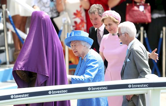 H.M The Queen removing a purple cloth to unveil a statue of Lestor Piggott, whilst wearing a blue outfit