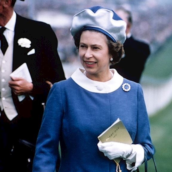 A young Queen wearing a blue dress with a white collar holding a racecard