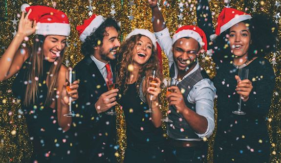 Group of men and women laughing in Christmas hats