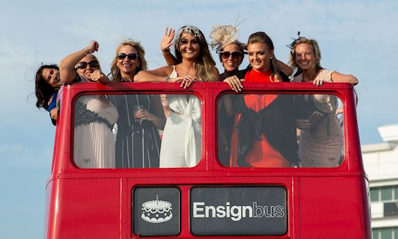 Group of racegoers on an open top red bus